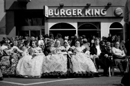 "Burger Queens Women wearing the traditional ""Fallera"" costume sit outside a less traditional establishment"